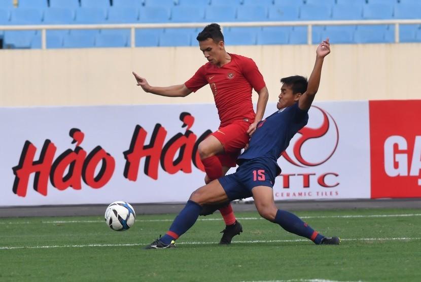 Pesepak bola tim nasional U-23 Indonesia Osvaldo Ardiles (kiri) berupaya melewati pesepak bola tim nasional U-23 Thailand Saringkan Promsupa (kanan) pada pertandingan perdana Grup K kualifikasi Piala Asia U-23 AFC 2020, di Stadion Nasional My Dinh, Hanoi, Vietnam, Jumat (22/3/2019).