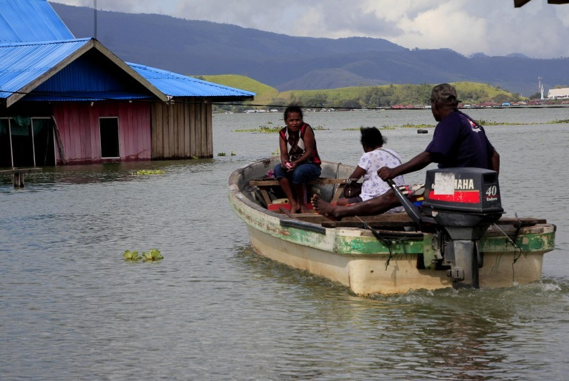 Warga menggunakan perahu menuju rumahnya yang terendam banjir akibat meluapnya Danau Sentani dampak dari banjir bandang Sentani di Kampung Yoboi, Danau Sentani, Sentani, Jaya Pura, Papua, Jumat (22/3/2019).