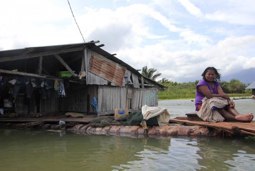 Seorang warga duduk di halaman rumahnya yang terendam banjir akibat meluapnya Danau Sentani dampak dari banjir bandang Sentani di Kampung Yoboi, Danau Sentani, Sentani, Jaya Pura, Papua, Jumat (22/3/2019).