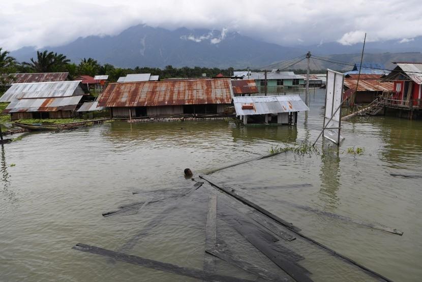 Warga merngumpulkan papan yang terbawa aliran air banjir yang merendam kampung mereka di Kampung Yoboi, Danau Sentani, Sentani, Jaya Pura, Papua, Jumat (22/3/2019).