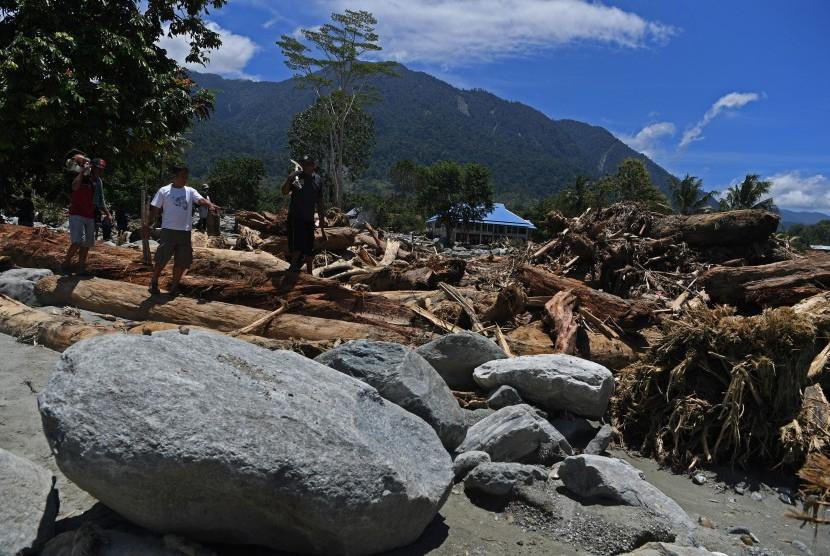 Sejumlah warga melintas di antara bongkahan kayu dan batu yang terbawa arus banjir bandang di Kampung Hinekomba, Sentani, Jayapura, Papua, Sabtu (23/3/2019).