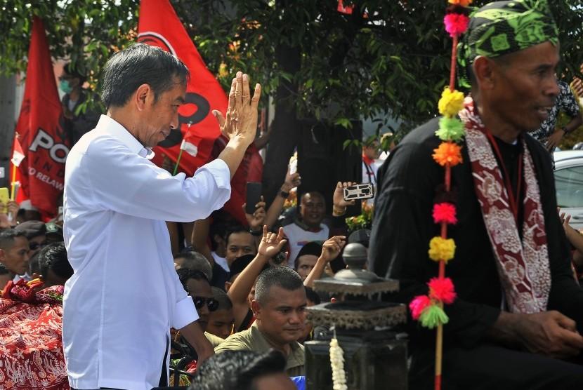 Capres nomor urut 01 Joko Widodo (kiri) menyapa warga saat tiba di Stadion Maulaya Yusuf untuk menghadiri Kampanye Terbuka di Ciceri, Serang, Banten, Ahad (24/3/2019).