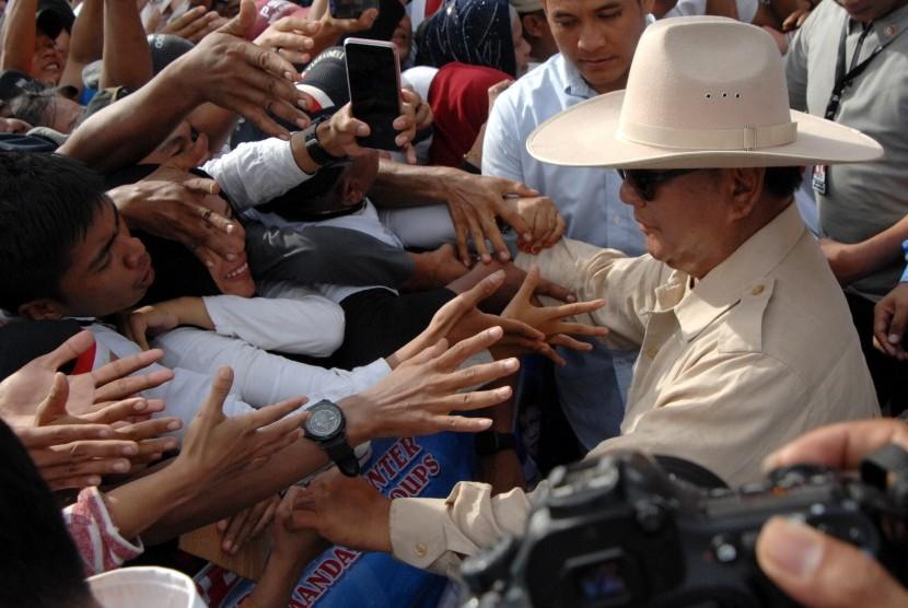 Calon Presiden nomor urut 02 Prabowo Subianto (kanan) menyapa pendukungnya saat berkampanye di lapangan Karebosi, Makassar, Sulawesi Selatan, Ahad (24/3/2019).