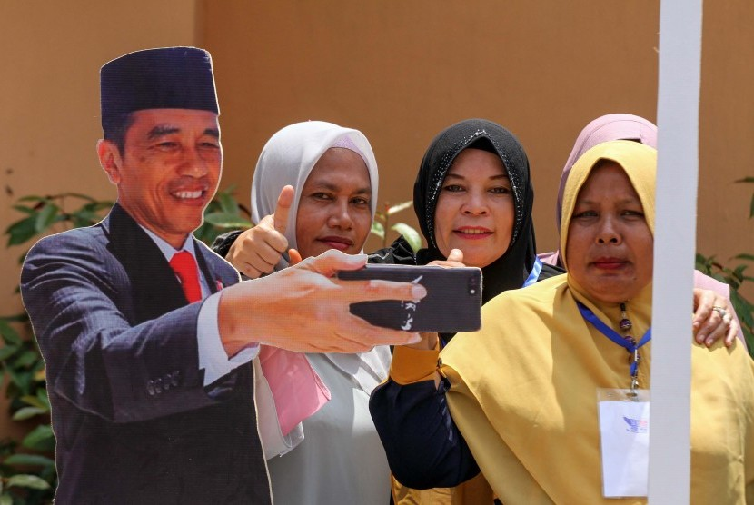 Sejumlah kaum perempuan pendukung calon Presiden nomor urut 01 Joko Widodo – Ma'ruf Amin berfoto dengan spot photo Jokowi usai kampanye terbuka Jokowi di Lhokseumawe, Aceh, Selasa (26/3/2019).