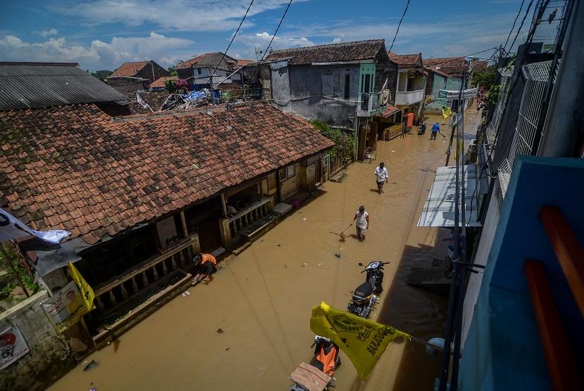Warga melintasi banjir yang menggenangi Desa Bojongasih, Dayeuhkolot, Kabupaten Bandung, Jawa Barat, Rabu (27/3/2019).