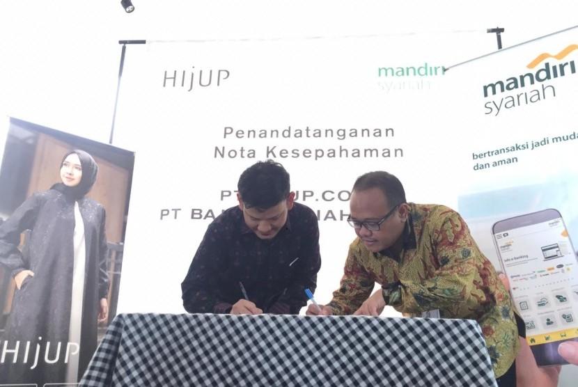Direktur Technology & Operation Mandiri Syariah Achmad Syafii (kanan) bersama Chief of Business Operation & Sales Officer HIJUP Akli Djumadie (kiri) menandatangani nota kesepahamantentang layanan jasa dan produk perbankan berdasarkan prinsip syariah di Living Stone, Bali, Senin (1/4).