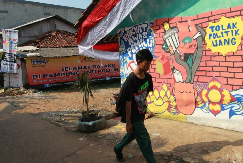 Warga melintasi kampung tematik yang bertemakan Kampung Anti Politik Uang di Pondok Aren, Tangerang Selatan, Banten, Kamis (4/4/2019).