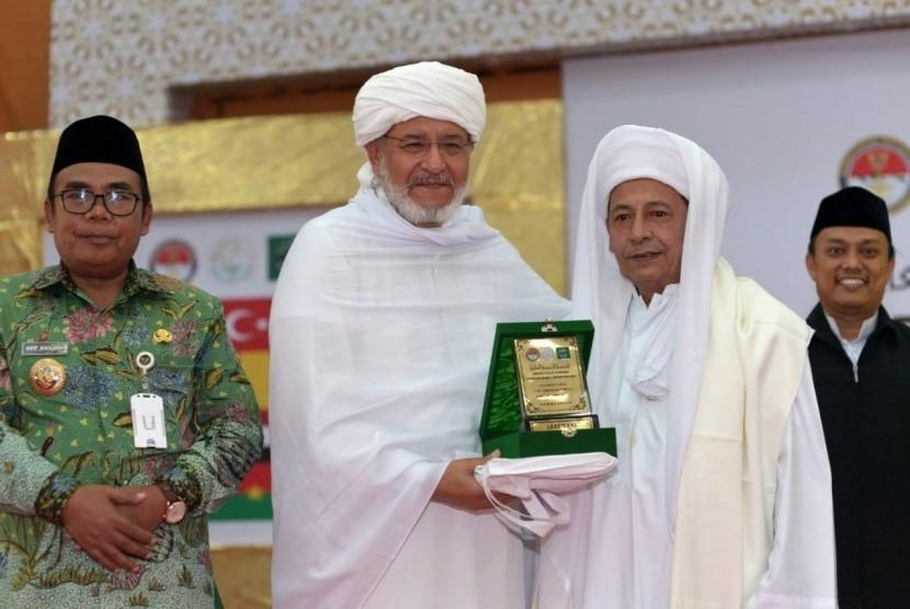Syekh Muhammad As-Syuhumi Al-Idrisi asal Libya (kedua kiri) menerima cenderamata berupa plakat dari Habib Luthfi bin Ali bin Yahya (kanan) pada agenda penutupan Konferensi Ulama Sufi Internasional di Pekalongan, Jawa Tengah, Rabu (10/4).