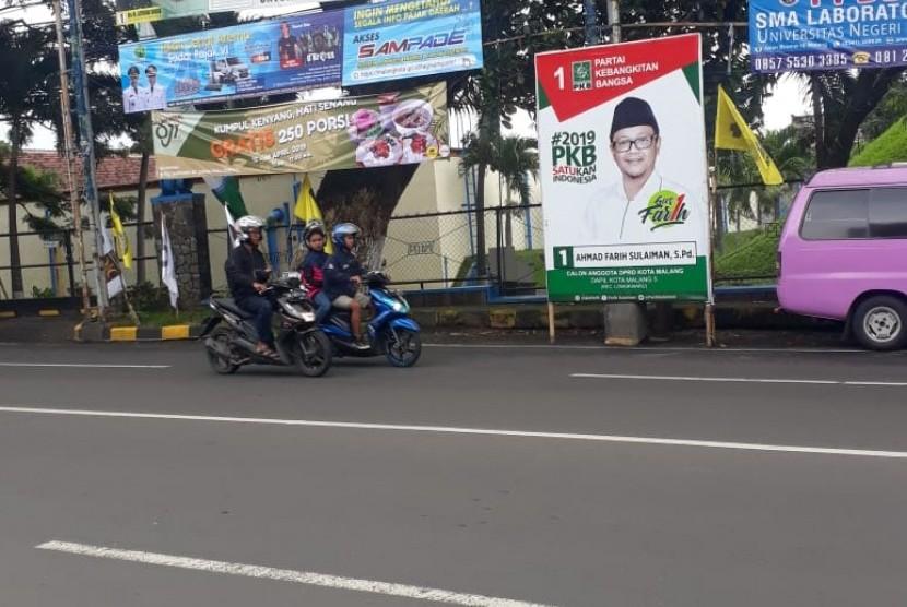 Sejumlah Alat Peraga Kampanye (APK) masih berdiri tegak di Jalan Dinoyo, Malang, Ahad (14/4).