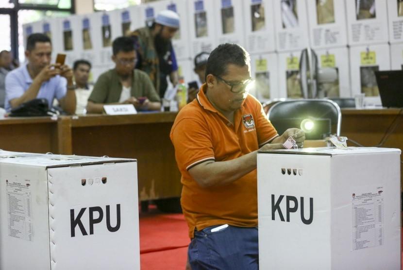 Petugas Panitia Pemilihan Kecamatan (PPK) membuka kotak suara yang berisi surat suara Pemilu Serentak 2019 untuk dilakukan rekapitulasi surat suara di tingkat Kecamatan di GOR Mangga Dua Selatan, Sawah Besar, Jakarta Pusat, Jumat (19/4/2019).