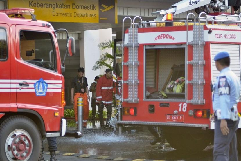 Petugas pemadam kebakaran bersiaga saat melakukan upaya pemadaman kebakaran yang terjadi di kawasanTerminal Keberangkatan Domestik Bandara Internasional I Gusti Ngurah Rai, Bali, Jumat (19/4/2019).