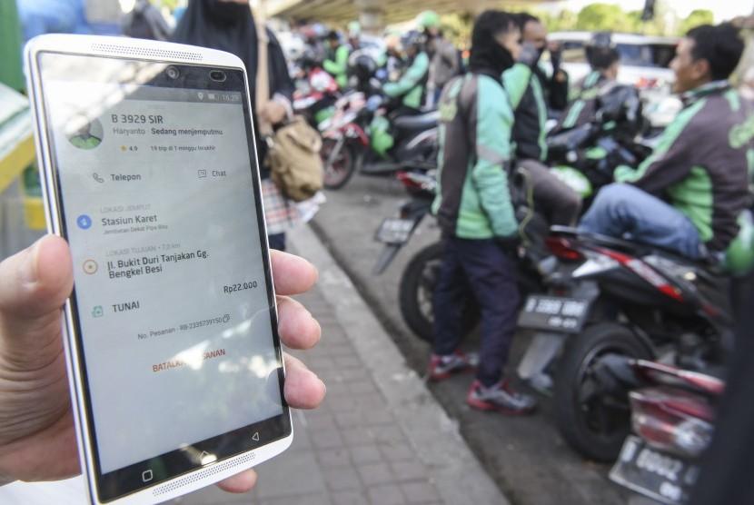 Calon penumpang menunjukan tarif ojek daring di Jakarta, Kamis (2/5/2019).