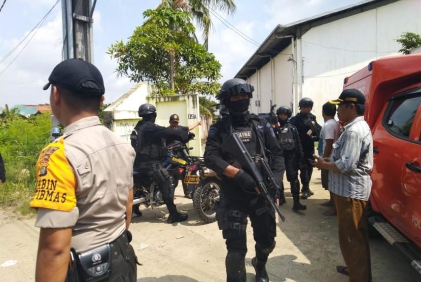 Seorang pengendara sedang melintas di depan lokasi penggerebekan terduga teroris di RT 11 RW 04, Desa Kedung Pengawas, Babelan, Kabupaten Bekasi, Sabtu (4/5). Penggerebekan oleh Tim Densus 88 pada pukul 04.00 WIB itu mengakibatkan 1 orang terduga teroris tewas ditempat.