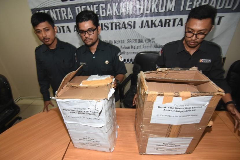 Petugas Bawaslu Jakarta Pusat menunjukkan kardus berisi ribuan form C1 Pemilu yang diamankan polisi dari sebuah mobil yang melaju di kawasan Menteng, Jakarta, di Gedung Bawaslu Jakarta Pusat, Senin (6/5/2019).