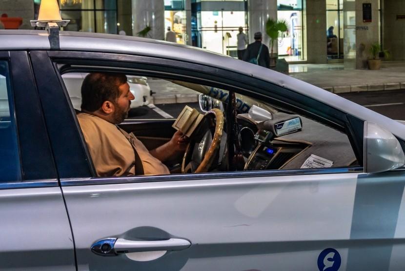 Seorang pengemudi taksi bertadarus Alquran saat menunggu penumpang di sekitar Masjid Nabawi, Madinah, Arab Saudi, Rabu (8/5/2019).