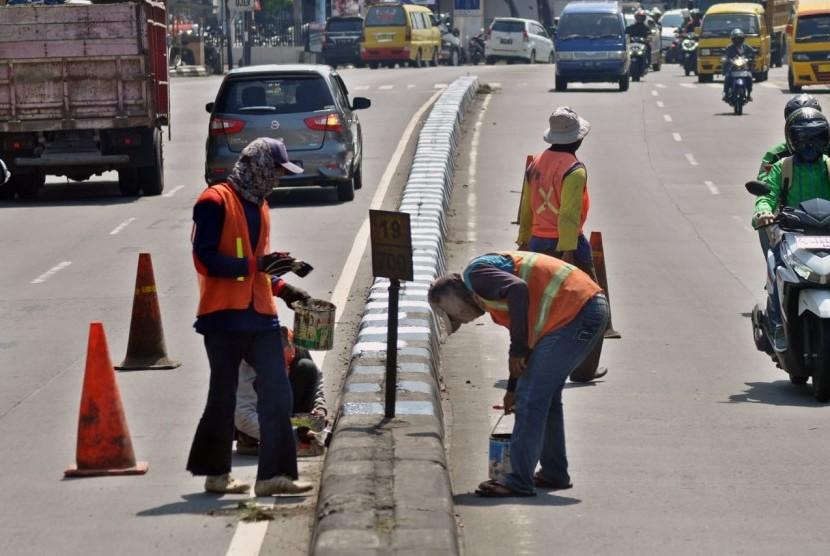 Pekerja PT Adhi Karya melakukan pengecatan median jalan di KM 19+700 di ruas Jalan Diponegoro Ungaran, Kabupaten Semarang, Jumat (10/5). Pekerjaan pemeliharaan jalan KBK ruas Banyumanik- Bawen ini juga diperuntukkan bagi penyiapan jalur utama non tol untuk mudik Lebaran tahun ini.