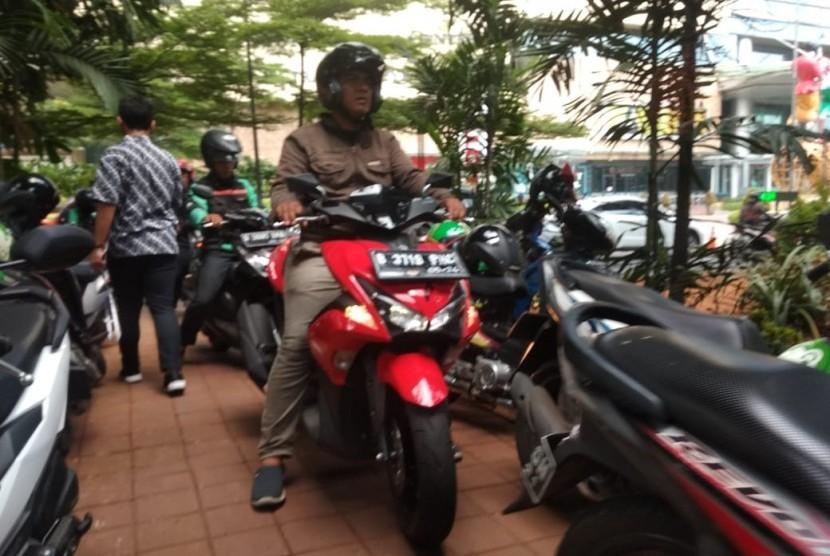 Sejumlah pengemudi ojek online memarkir kendaraannya di Taman depan Mall Ciputra World, Karet Kuningan Jakarta Selatan,  Selasa (14/5).