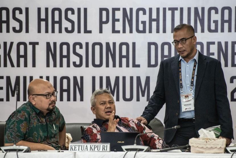 Ketua KPU Arief Budiman (tengah), para Komisioner KPU Hasyim Asy'ari (kanan) dan Ilham Saputra (kiri) berbincang di sela Rapat Pleno Rekapitulasi Hasil Penghitungan dan Perolehan Suara Tingkat Nasional Dalam Negeri dan Penetapan Hasil Pemilu 2019 di kantor KPU, Jakarta, Rabu (15/5/2019).