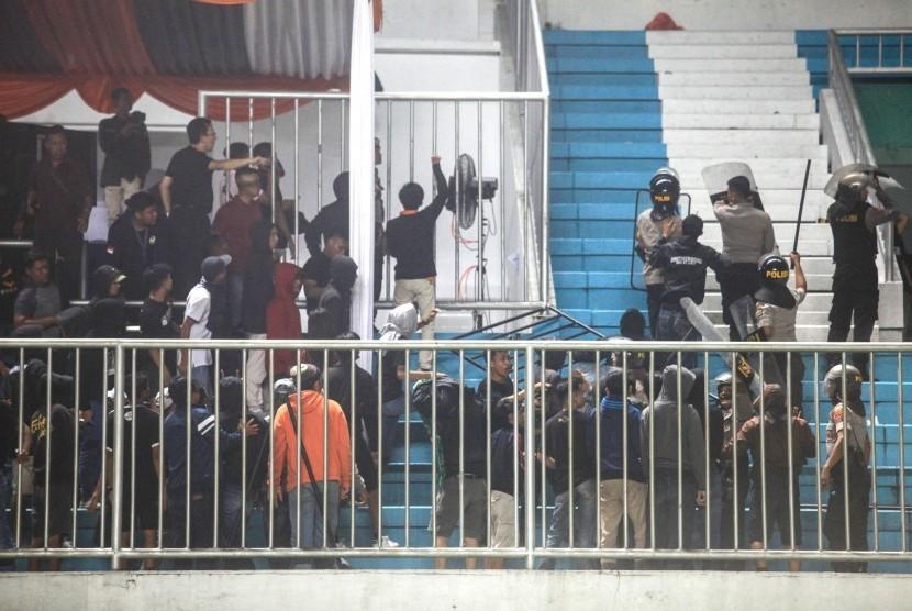 Polisi menghalau pendukung yang ricuh saat pertandingan Liga 1 antara PSS Sleman melawan Arema FC di Stadion Maguwoharjo, Sleman, DI Yogyakarta, Rabu (15/5/2019).