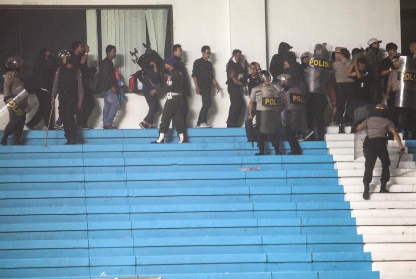 Polisi mengamankan penonton saat terjadi kericuhan pendukung saat pertandingan perdana Liga 1 antara PSS Sleman melawan Arema FC di Stadion Maguwoharjo, Sleman, DI Yogyakarta, Rabu (15/5/2019).