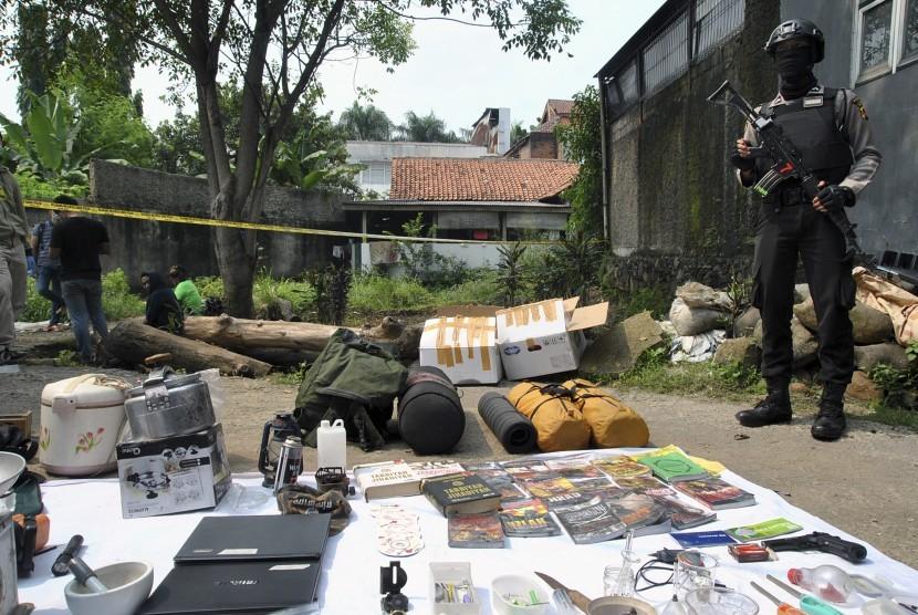 Seorang anggota polisi dengan senjata lengkap berada di dekat barang bukti terduga teroris di Kampung Nanggewer Kaum, Cibinong, Kabupaten Bogor, Jawa Barat, Sabtu (18/5/2019).