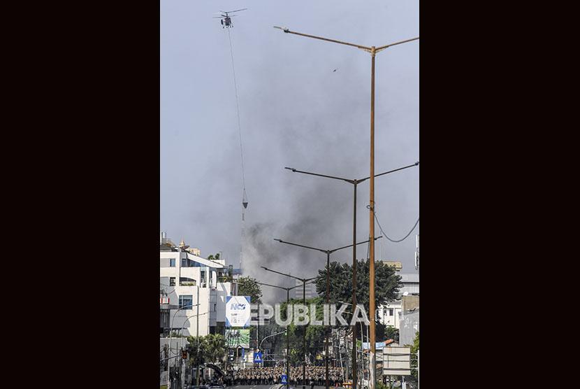 Helikopter menyiramkan air untuk memadamkan ban yang dibakar oleh massa saat kerusuhan di Jalan Slipi 1, Slipi, Jakarta, Rabu (22/5/2019).