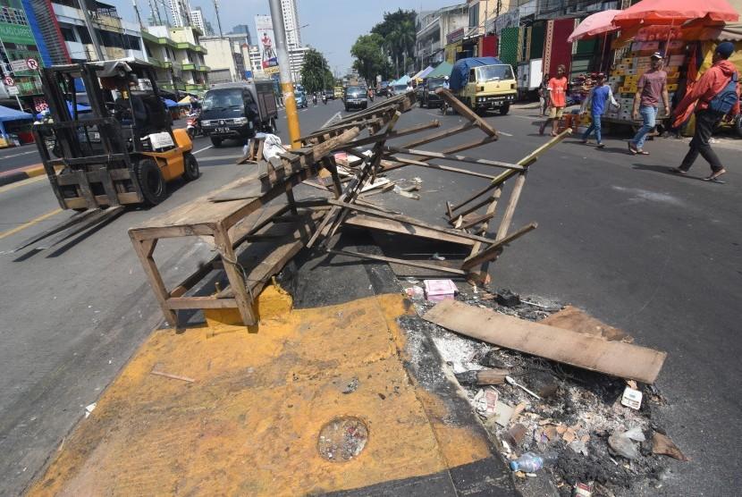Warga melintas di wilayah terdampak kerusuhan Aksi 22 Mei di kawasan Tanah Abang, Jakarta, Kamis (23/5/2019).