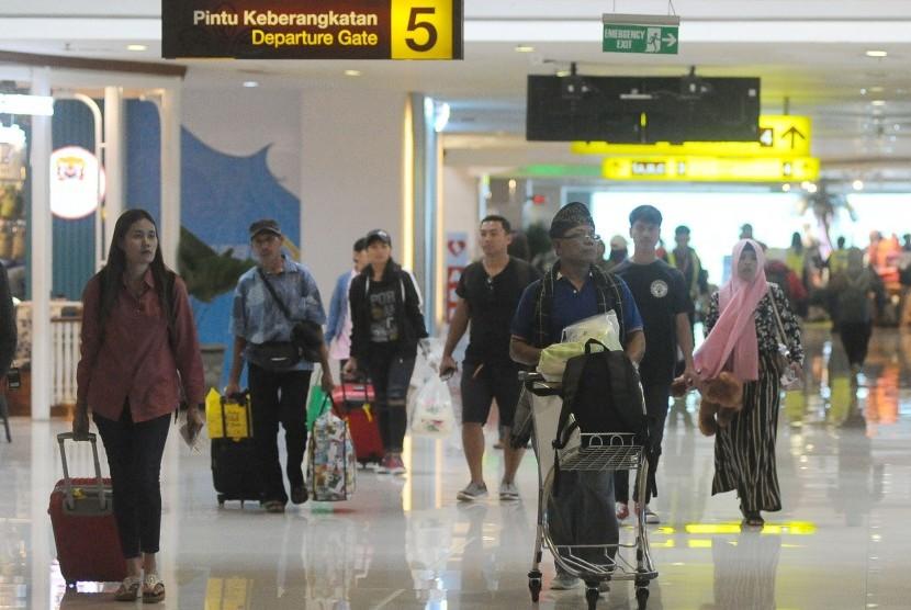 Calon penumpang pesawat udara membawa barang bawaan di Terminal Keberangkatan Domestik Bandara Internasional I Gusti Ngurah Rai, Bali, Jumat (31/5/2019).