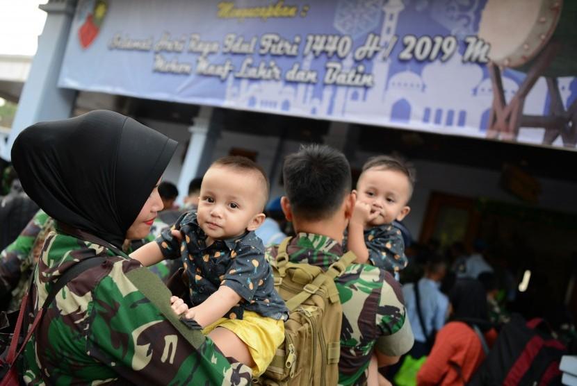 Seorang prajurit wanita TNI bersama anaknya menunggu daftar panggil ketika akan mudik di Lanud Halim Perdanakusuma, Jakarta Timur, Sabtu (1/6/2019).