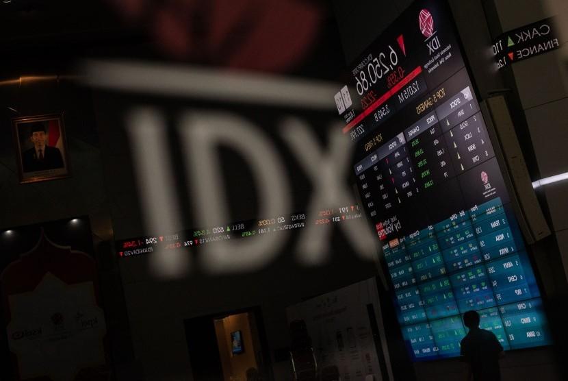 Karyawan melintas di dekat layar pergerakan saham di gedung Bursa Efek Indonesia (BEI), Jakarta, Jumat (14/6/2019).