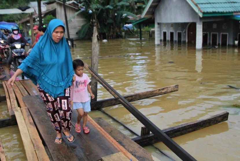 Warga melintasi jembatan darurat yang baru dibuat akibat terus naiknya ketinggian banjir di Kelurahan Sampara, Konawe, Sulawesi Tenggara, Jumat (14/6/2019).