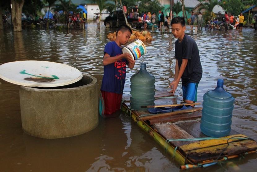 Warga mengambil air di sumur yang telah bercampur air banjir di Desa Wanuamandala, Konawe, Sulawesi Tenggara, Sabtu (15/6/2019).