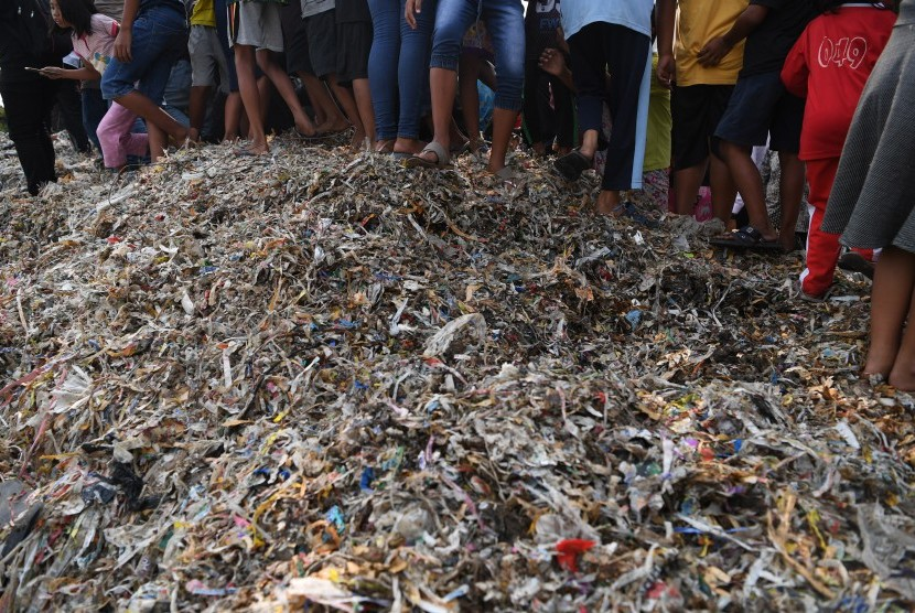 Warga berdiri di atas tumpukan sampah plastik impor di Desa Bangun di Mojokerto, Jawa Timur.