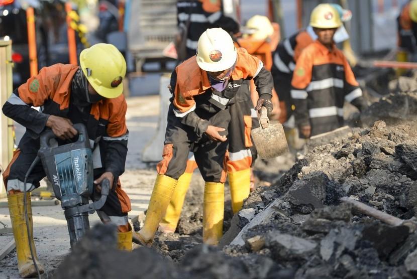 Pekerja membongkar trotoar lama di Jalan Cikini Raya depan Taman Ismail Marzuki (TIM), Jakarta, Rabu (19/6/2019).