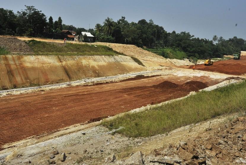 Sejumlah pekerja dengan menggunakan alat berat menyelesaikan proyek pembangunan jalan Tol Serang-Panimbang di Kampung Parongpong, Cukeusal, Serang, Banten, Jumat (21/6/2019).