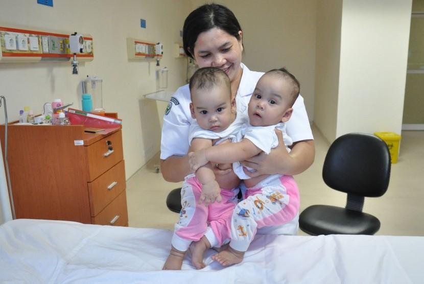 Perawat memegang bayi kembar siam di Rumah Sakit Umum Pusat (RSUP) H Adam Malik Medan, Sumatera Utara, Senin (1/7/2019).