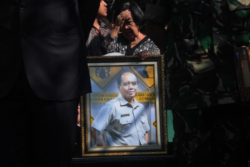 Seorang kerabat membawa foto Almarhum Kepala Pusat Data Informasi dan Humas Badan Nasional Penanggulangan Bencana (BNPB) Sutopo Purwo Nugroho saat pemakaman di Tempat Pemakaman Umum Sonolayu, Boyolali, Jawa Tengah, Senin (8/7/2019)