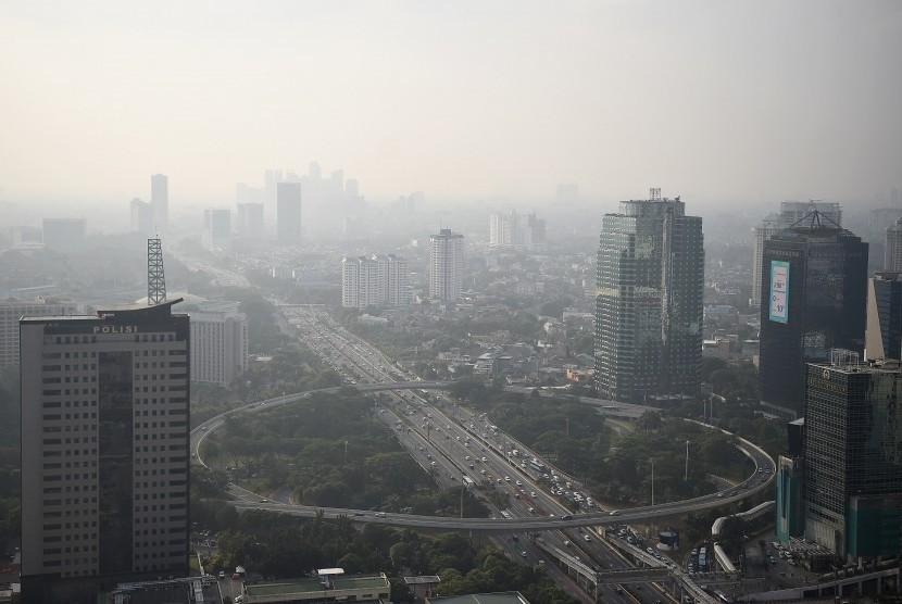 Gedung bertingkat tersamar kabut polusi udara di Jakarta, Senin (8/7/2019).