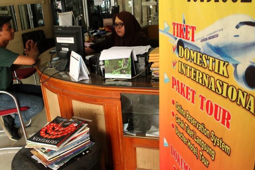 Pekerja tiketing melayani konsumen tiket pesawat, di salah satu agen tour and travel, di Bekasi, Jawa Barat, Selasa (9/7/2019).
