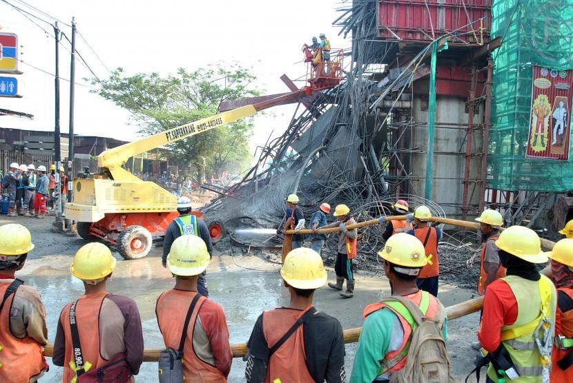 Sejumlah pekerja membersihkan material coran semen di lokasi ambruknya salah satu tiang penyangga proyek pembangunan Tol Bogor Outer Ring Road (BORR) Seksi IIIA simpang Yasmin-Semplak di jalan raya KH Sholeh Iskandar, Kelurahan Cibadak, Tanah Sareal, Kota Bogor, Jawa Barat, Rabu (10/7/2019).