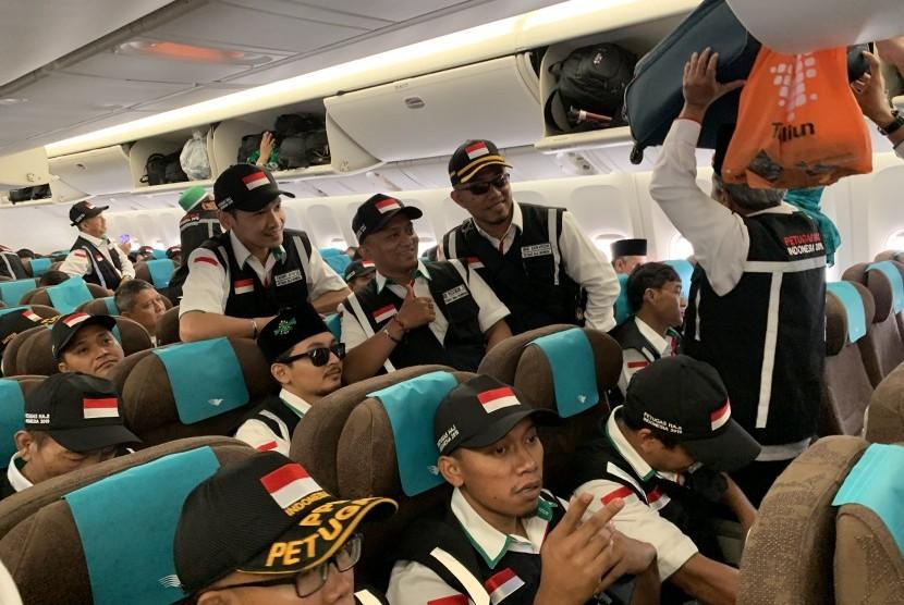 Para petugas haji berpose di dalam pesawat Garuda Indonesia yang akan mengangkut mereka ke Tanah Suci dari Bandara Soekarno Hatta, Banten, Selasa (9/7/2019).