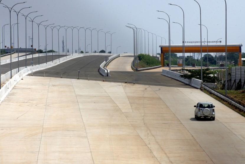 Mobil melintas di proyek pembangunan Tol Cimanggis-Cibitung Seksi 1A yang belum beroperasi di Cimanggis, Depok, Jawa Barat, Kamis (11/7/2019).