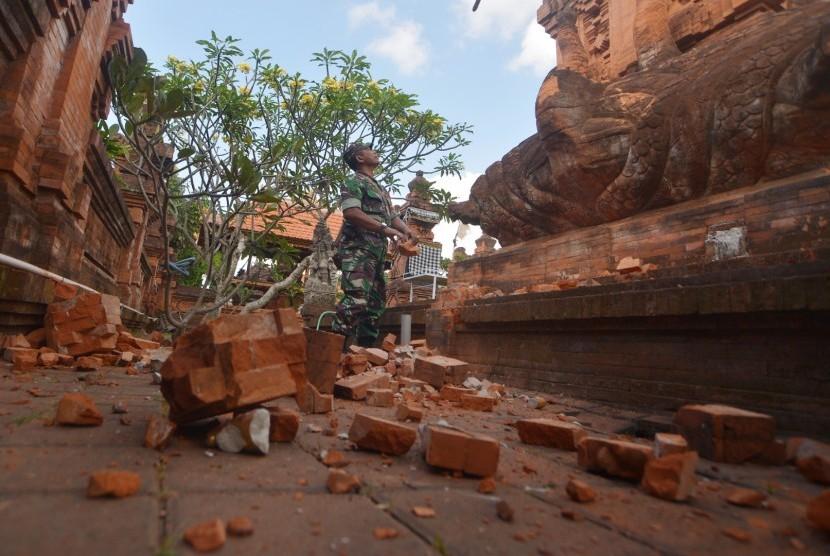 Prajurit TNI memantau kerusakan pada bagian candi yang runtuh akibat gempa di Pura Lokanatha, Denpasar, Bali, Selasa (16/7/2019).