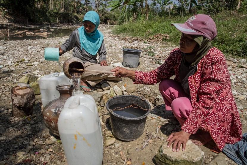 Warga mengambil air dari lubang yang digali di dasar sungai yang kering di Desa Glagah, Tangen, Sragen, Jawa Tengah, Selasa (16/7/2019).