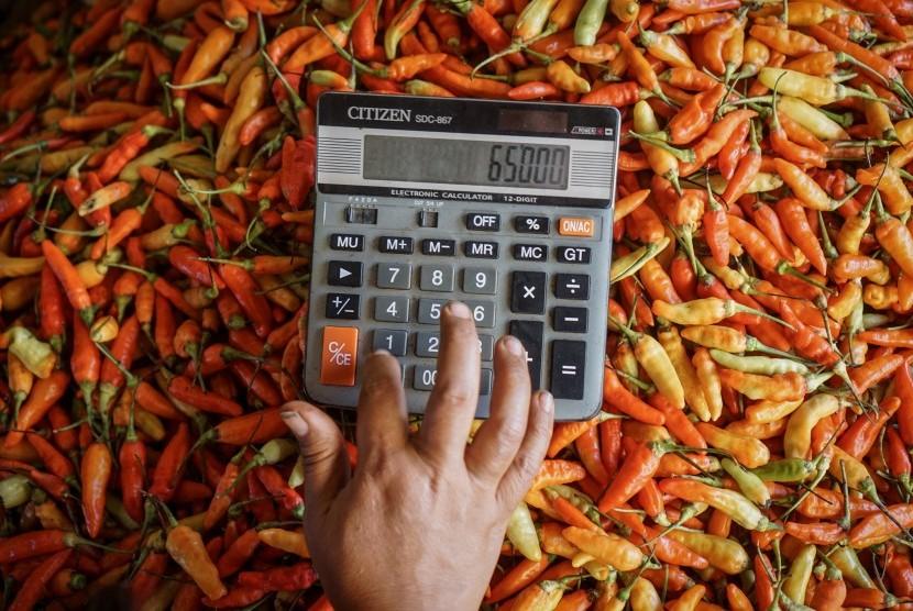 Pedagang menghitung harga cabai dengan kalkulator.