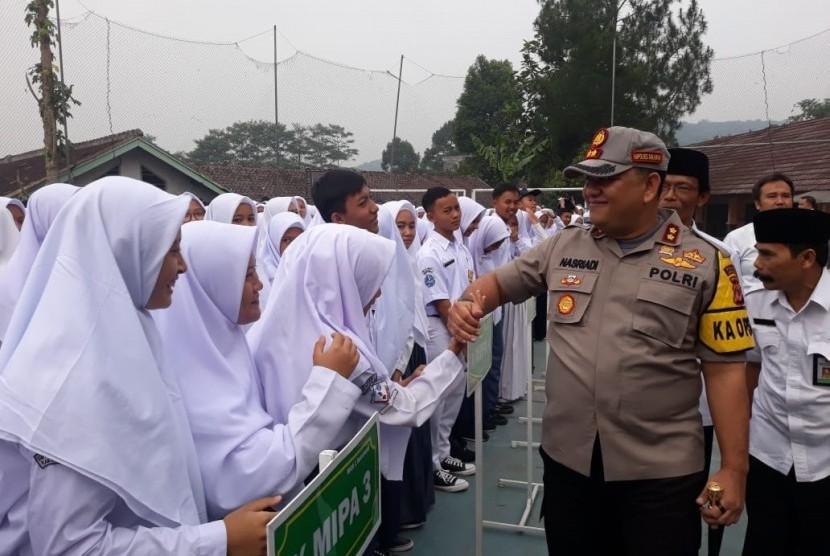 Para pelajar MAN 1 Kabupaten Sukabumi bersalaman dengan Kapolres Sukabumi AKBP Nasriadi setelah mengikuti upacara bendera dan ramai berita pengibaran bendera tauhid, Senin (22/7)