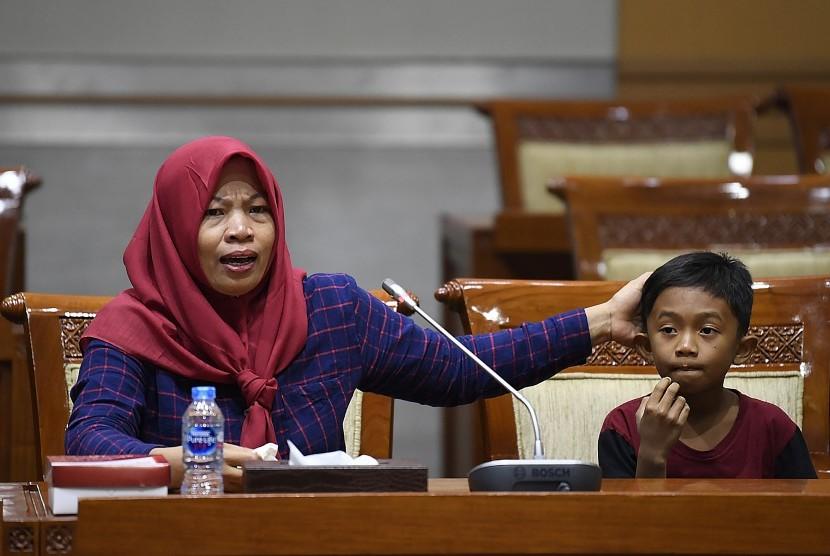 Terpidana kasus pelanggaran Undang-Undang Transaksi dan Informasi Elektronik (UU ITE), Baiq Nuril Maknun (kiri) didampingi anaknya menyampaikan tanggapan saat rapat pleno Komisi III DPR terkait surat persetujuan amnesti di Kompleks Parlemen Senayan, Jakarta, Selasa (23/7/2019).