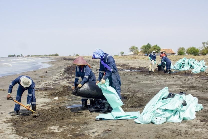 Petugas mengumpulkan tumpahan minyak mentah yang tercecer di Pesisir Pantai Mekarjaya, Karawang, Jawa Barat, Kamis (8/8/2019).