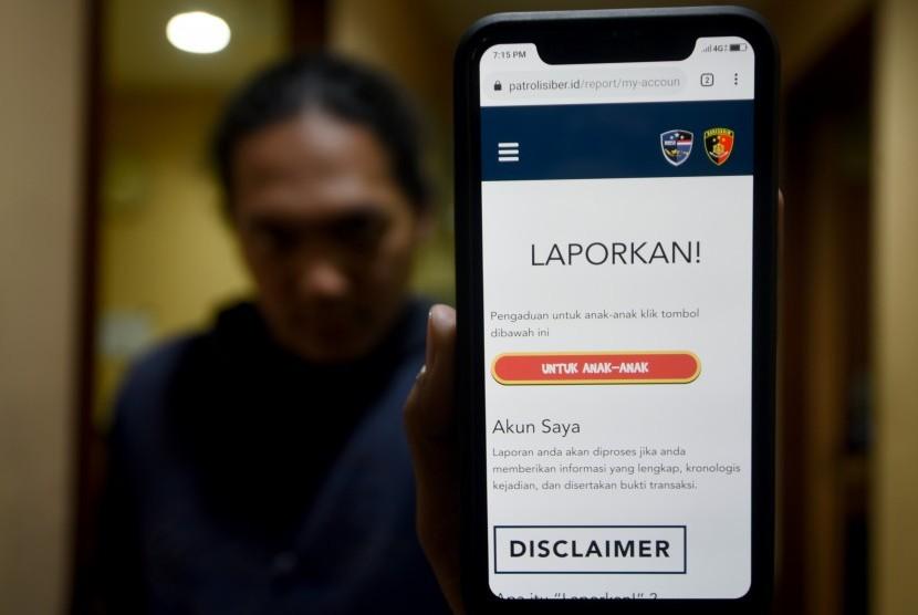 Warga menunjukkan aplikasi situs patrolisiber.id saat peluncuran di kantor Bareskrim Polri, Jalan Trunojoyo, Jakarta Selatan, Rabu (14/8/2019).