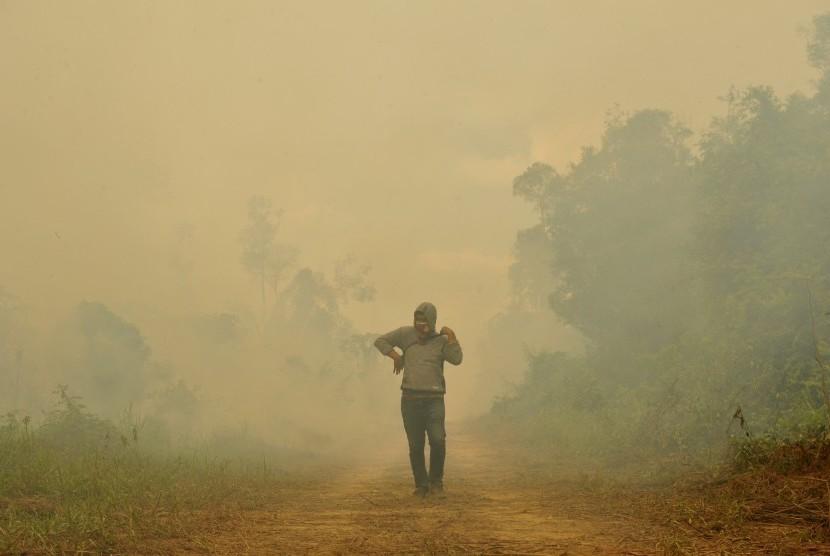 Warga berada di sekitar lahan gambut yang terbakar di Kumpeh Ulu, Muarojambi, Jambi, Kamis (15/8/2019).